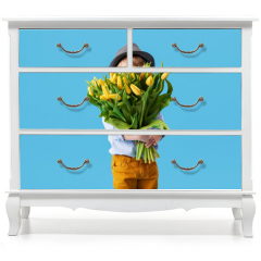 Naklejka na meble - Cute smiling child holding a beautiful bouquet of yellow tulips in front of his face isolated on blue. Little toddler boy gives a bouquet to mom