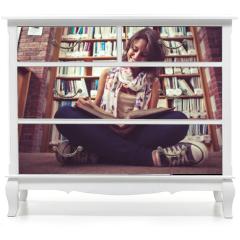 Naklejka na meble - Happy female student against bookshelf reading a book on the lib