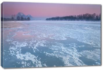 Obraz na płótnie canvas - Smoking chimneys over a misty and freezing river during dusk