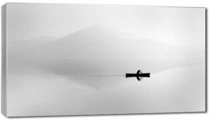 Obraz na płótnie canvas - Fog over the lake. Silhouette of mountains in the background. The man floats in a boat with a paddle. Black and white