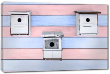 Obraz na płótnie canvas - tres cajas nido blancas sobre fondo de madera rosa y azul