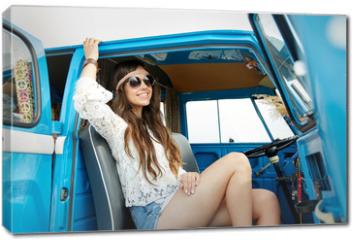 Obraz na płótnie canvas - smiling young hippie woman in minivan car