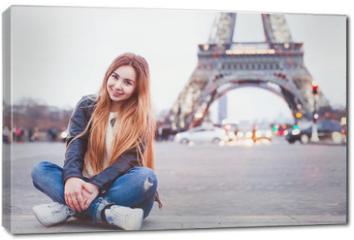 Obraz na płótnie canvas - smiling happy beautiful woman tourist in Paris looking at camera, portrait of caucasian girl near Eiffel Tower