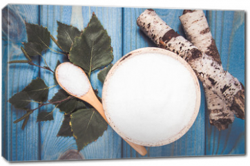 Obraz na płótnie canvas - Xylitol - sugar substitute. Birch sugar on blue wooden background.