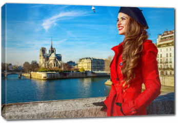 Obraz na płótnie canvas - tourist woman in red trench coat in Paris, France looking aside