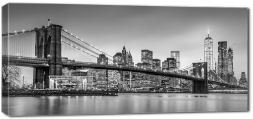 Obraz na płótnie canvas - Brooklyn bridge and New York City Manhattan downtown skyline at dusk with skyscrapers illuminated over East River panorama. Panoramic composition.