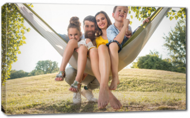 Obraz na płótnie canvas - Family portrait with a beautiful mother of two playful children swinging in a hammock while looking at camera next to her husband outdoors in summer