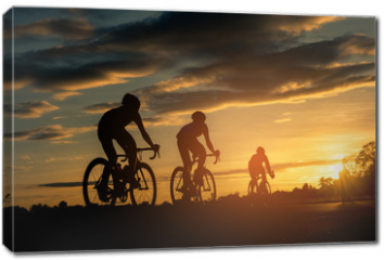 Obraz na płótnie canvas - The men ride  bikes at sunset with orange-blue sky background. Abstract Silhouette background concept.
