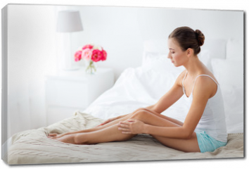 Obraz na płótnie canvas - people, beauty, depilation, epilation and bodycare concept - beautiful woman touching smooth leg skin on bed at home bedroom