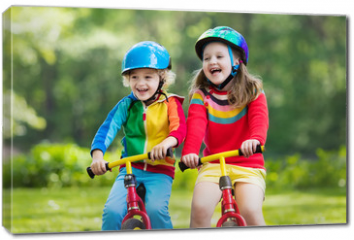Obraz na płótnie canvas - Kids ride balance bike in park