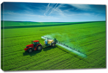 Obraz na płótnie canvas - Aerial view of farming tractor plowing and spraying on field