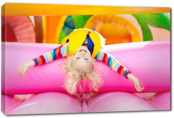 Obraz na płótnie canvas - Child jumping on playground trampoline. Kids jump.