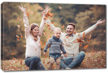 Obraz na płótnie canvas - Happy family having fun in autumn forest
