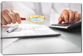 Obraz na płótnie canvas - Businessman Analyzing Financial Report With Magnifying Glass