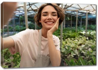 Obraz na płótnie canvas - Gardener standing over plants in greenhouse take a selfie by camera.