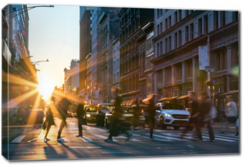 Obraz na płótnie canvas - Rays of sunlight shine on the busy people walking across an intersection in Midtown Manhattan in New York City