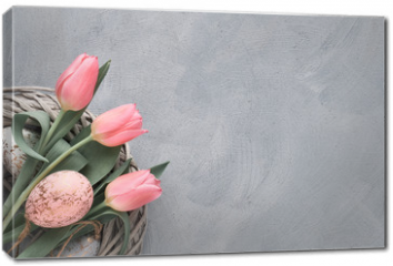 Obraz na płótnie canvas - Springtime or Easter background with pink tulips and Easter eggs in wattle ring on grey concrete, text space