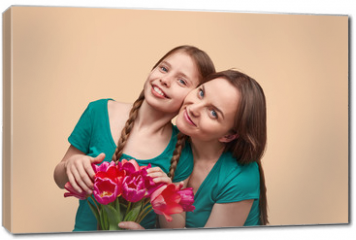 Obraz na płótnie canvas - Mother and daughter with flowers posing for camera