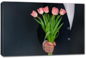 Obraz na płótnie canvas - man's hand giving a bouquet of pink tulips