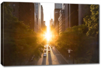Obraz na płótnie canvas - Sunlight shines on the buildings and cars along 42nd Street through Midtown Manhattan around the Manhattanhenge sunset in New York City