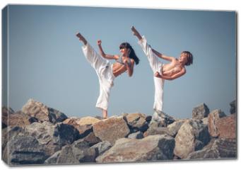 Obraz na płótnie canvas - Children training karate on the stone coast