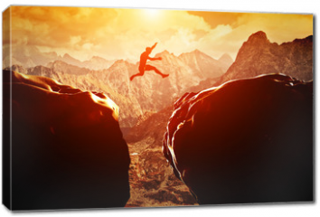 Obraz na płótnie canvas - Man jumping over precipice between two mountains at sunset