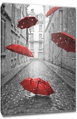 Obraz na płótnie canvas - Red umbrellas flying on the street. Conceptual image