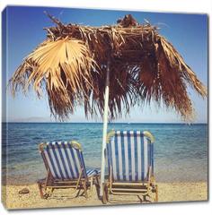 Obraz na płótnie canvas - Sunbeds with umbrella on the beach