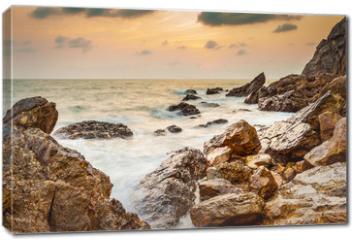 Obraz na płótnie canvas - Seascape coast of evening wave with rock and cloud on golden sky
