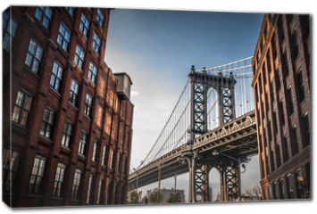 Obraz na płótnie canvas - Manhattan bridge seen from a narrow alley enclosed by two brick buildings on a sunny day in summer