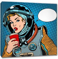 Obraz na płótnie canvas - Female astronaut drinking soda