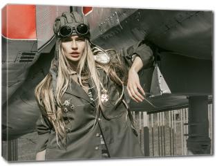 Obraz na płótnie canvas - Piękna dziewczyna w mundurze wojskowym ze sprzętem wojskowym.