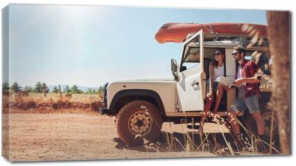 Obraz na płótnie canvas - Młoda para na wycieczce, sprawdzająca mape dojazdu