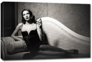 Obraz na płótnie canvas - Film noir style: elegant young woman lying on sofa and smoking cigarette. Black and white