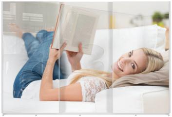 Panel szklany do szafy przesuwnej - lächelnde junge frau liest ein buch auf dem sofa