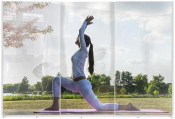 Panel szklany do szafy przesuwnej - Pretty woman doing yoga exercises in the park.
