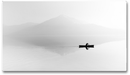Plakat - Fog over the lake. Silhouette of mountains in the background. The man floats in a boat with a paddle. Black and white
