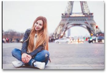 Plakat - smiling happy beautiful woman tourist in Paris looking at camera, portrait of caucasian girl near Eiffel Tower