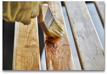 Plakat - Paint Brush in a can of varnish in preparation to stain the wood slats