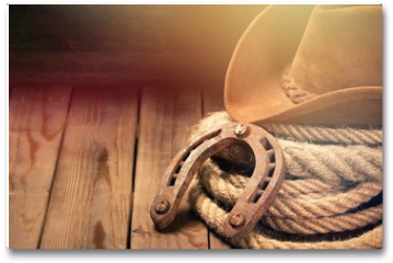 Plakat - Old horseshoe , lariat lasso and cowboy hat on background