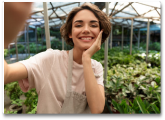 Plakat - Gardener standing over plants in greenhouse take a selfie by camera.