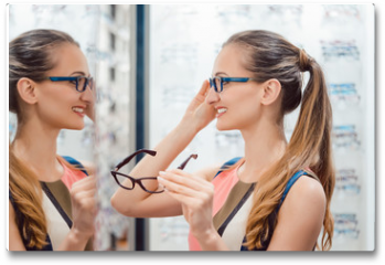 Plakat - Young woman in optometrists store checking her looks in mirror