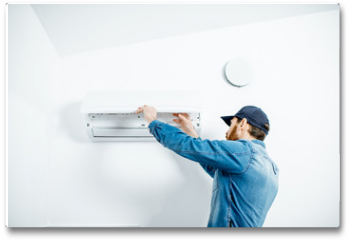 Plakat - Repairman in blue workwear serving the air conditioner changing filter on the white wall background