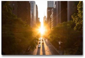 Plakat - Sunlight shines on the buildings and cars along 42nd Street through Midtown Manhattan around the Manhattanhenge sunset in New York City