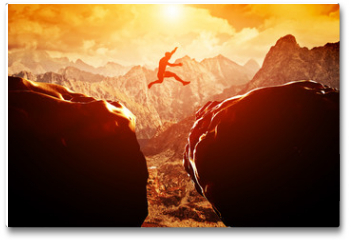 Plakat - Man jumping over precipice between two mountains at sunset