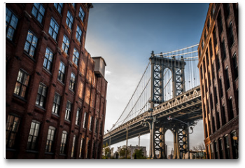 Plakat - Manhattan bridge seen from a narrow alley enclosed by two brick buildings on a sunny day in summer
