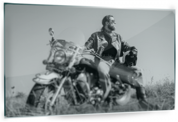 Panel szklany do kuchni - Portrait of a young man with beard sitting on his cruiser motorcycle and looking to the sun. Man is wearing leather jacket and blue jeans. Low point of view. Tilt lens blur effect. Black and white