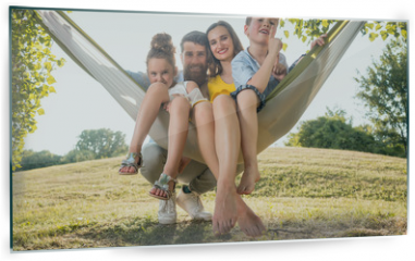 Panel szklany do kuchni - Family portrait with a beautiful mother of two playful children swinging in a hammock while looking at camera next to her husband outdoors in summer