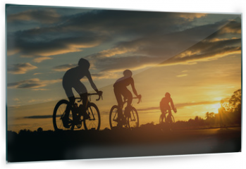 Panel szklany do kuchni - The men ride  bikes at sunset with orange-blue sky background. Abstract Silhouette background concept.