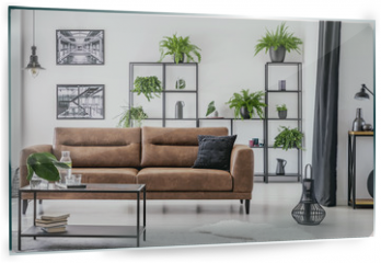 Panel szklany do kuchni - Table in front of leather sofa in white apartment interior with lamp, posters and plants. Real photo